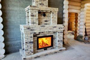 Большой интерьерный камин со стеклянной дверцей из кирпича ручной формовки