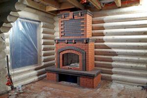 Большой пристенный камин из гладкого кирпича в бревенчатом доме