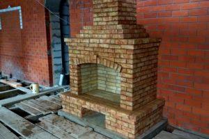 Большой пристенный камин из кирпича ручной формовки